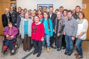 Stolz präsentiert die Künstlergruppe ihre insgesamt 20 Werke im Foyer des Wallenhorster Rathauses, hier mit Margret Terglane (links) von der Gemeindeverwaltung, Bürgermeister Otto Steinkamp (Mitte) und HHO-Geschäftsführer Heiner Böckmann (6. von rechts). Foto: Gemeinde Wallenhorst / Thomas Remme