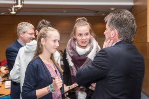 """Spaß beim """"Politiker-Bingo"""" hatten Justin Gespannt warteten die Schülerinnen Anne Westermann (links) und Jona Norina Kenning auf die Antworten des Ratsvorsitzenden Hans Stegemann. Foto: Gemeinde Wallenhorst / Thomas Remme"""