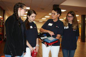 Maria Richter vom Malteser-Hilfsdienst mit den Schulsanitäterinnen der Thomas-Morus-Schule bei der Inbetriebnahme des lebensrettenden Defibrillators. Foto: TMS