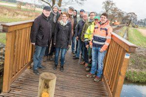 Mitglieder des Arbeitskreises Dorferneuerung, Vertreter der Gemeindeverwaltung und der Baufirmen sowie Bürgermeister Otto Steinkamp (3. von rechts) präsentieren die neue Brücke am Erftenbecksweg. Foto: Thomas Remme
