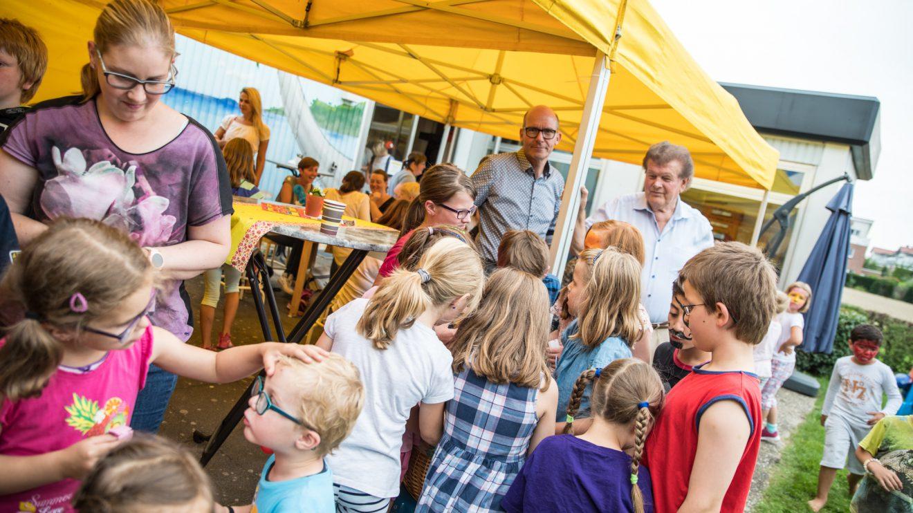 Rüdiger Mittmann und Alfons Schwegmann (hinten, von links) verteilen Süßigkeiten an die Kinder. Foto: Thomas Remme