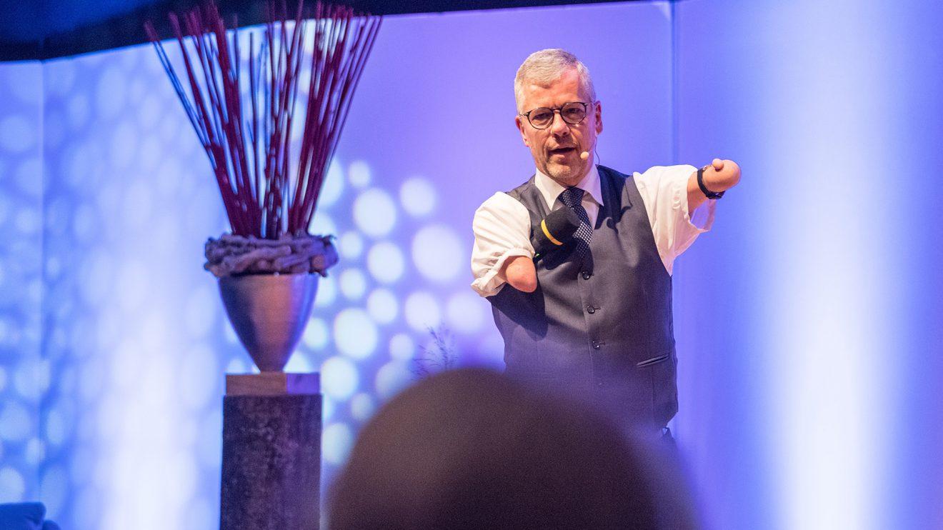 """Pfarrer Rainer Schmidt """"predigt"""" humorvoll auf der Bühne. Foto: Thomas Remme"""