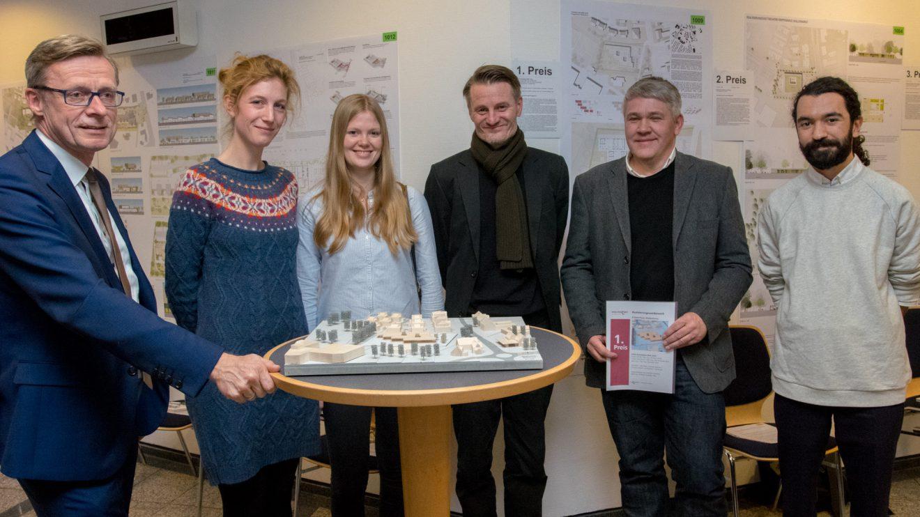 Bürgermeister Otto Steinkamp (links) und das Team des Architekturbüros LHVH am Modell des Krippenhauses. Foto: Gemeinde Wallenhorst / André Thöle