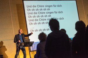 Die Chöre singen nicht nur für ihn, sondern vor allem für sich selbst – David Rauterberg unterstützt auf der Bühne mit Musik und Text. Foto: Thomas Remme