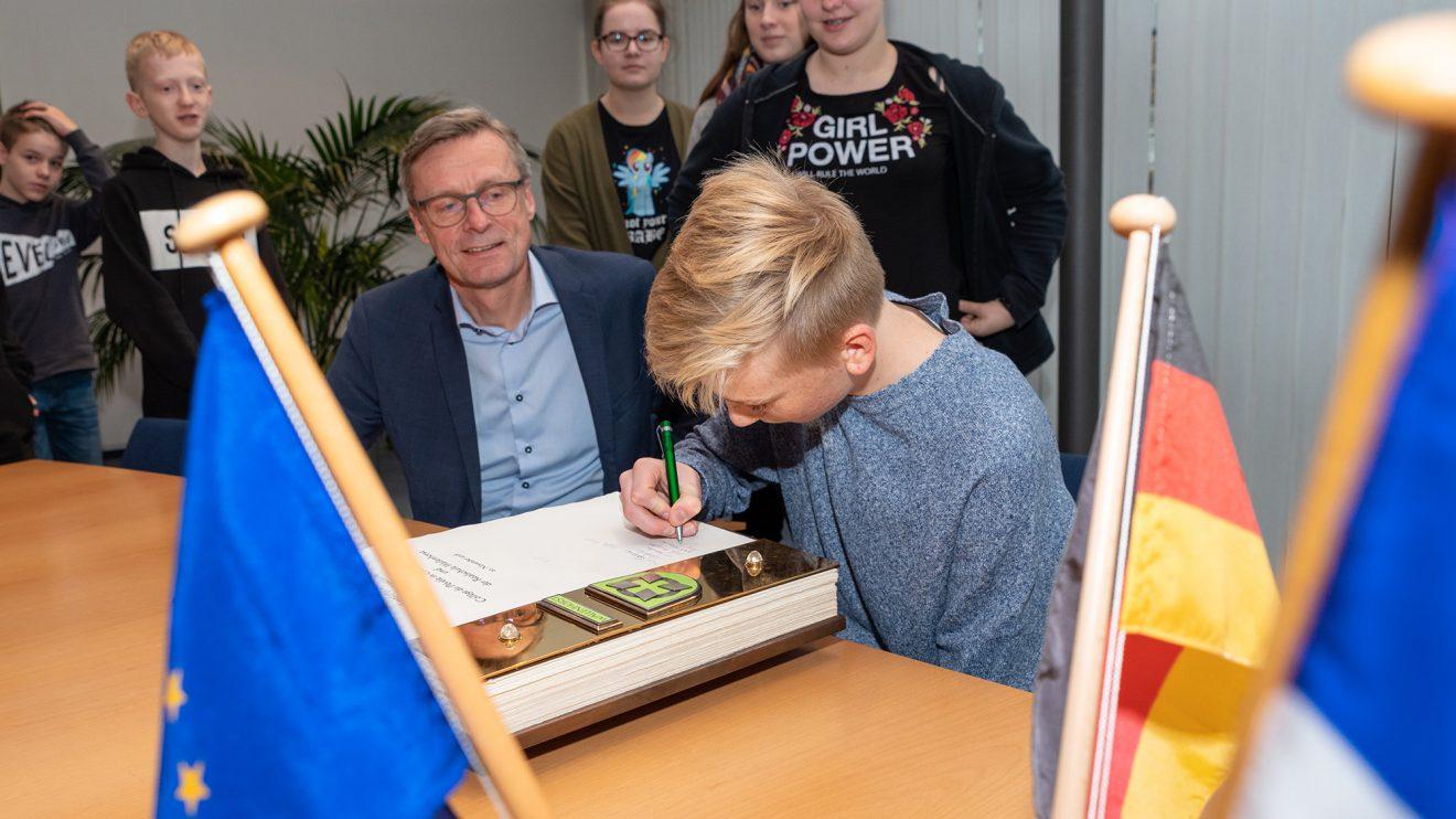 Die Schülerinnen und Schüler tragen sich im Beisein von Bürgermeister Otto Steinkamp ins Goldene Buch der Gemeinde Wallenhorst ein. Foto: Thomas Remme