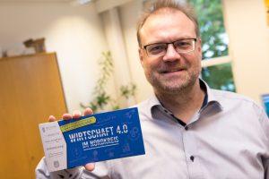 """Wallenhorsts Wirtschaftsförderer Frank Jansing präsentiert den Flyer """"Wirtschaft 4.0 im Nordkreis"""". Foto: André Thöle"""