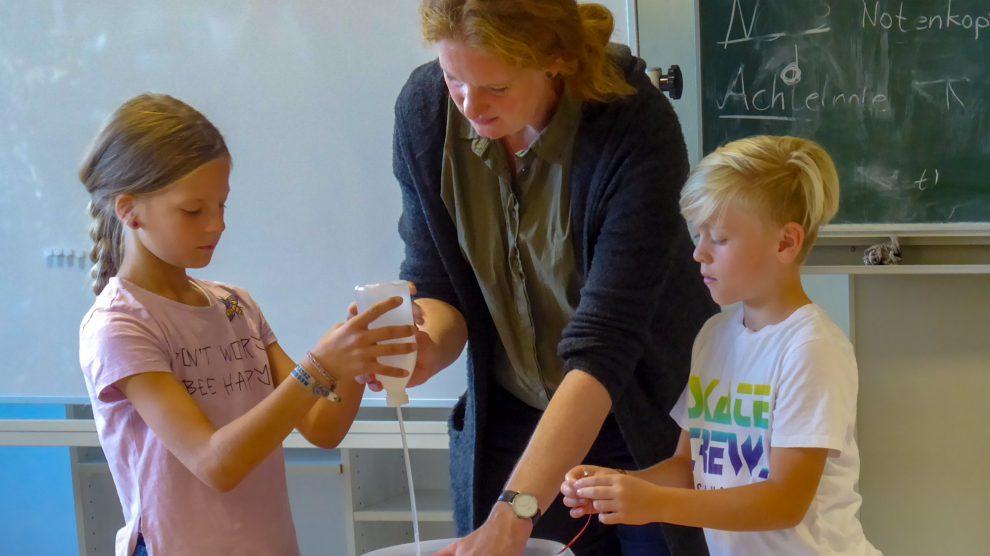 Franzis Brüse erläutert den Kindern anhand von kleinen Experimenten das Thema Energie von der Erzeugung bis zur Einsparung. Foto: Silke Schrempel / St.-Bernhard-Schule Rulle