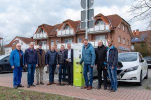 Bürgermeister Otto Steinkamp (4. von rechts), Björn Fütz (2. von rechts) und Stefan Sprenger (rechts) nehmen die E-Ladesäule gemeinsam mit Vertretern der Ratsfraktionen in Betrieb. Foto: Gemeinde Wallenhorst /André Thöle