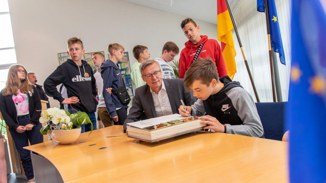 Die Jugendlichen aus Olsztyn tragen sich im Beisein von Bürgermeister Otto Steinkamp ins Goldene Buch der Gemeinde Wallenhorst ein. Foto: Gemeinde Wallenhorst / André Thöle