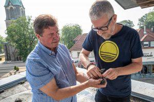 Udo Stangier (links) und Axel Degen beringen die Jungvögel auf dem Dach des Rathauses. Foto: Gemeinde Wallenhorst / Thomas Remme