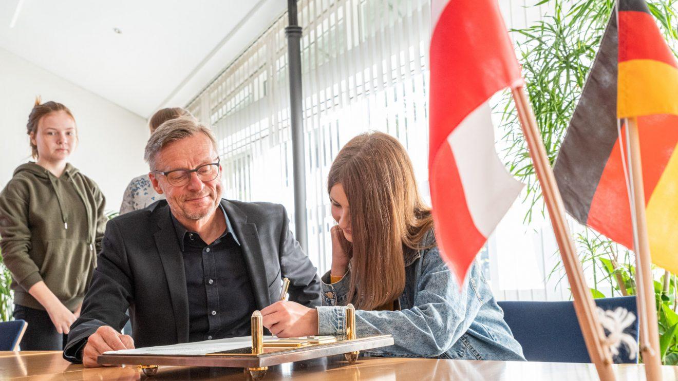 Die Jugendlichen tragen sich im Beisein von Bürgermeister Otto Steinkamp ins Goldene Buch der Gemeinde Wallenhorst ein. Foto: Gemeinde Wallenhorst / Thomas Remme