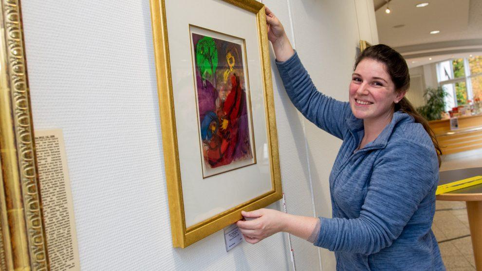 Nina Ollmert (Kunsthandlung Hülsmeier) hängt die Lithographien im Foyer des Wallenhorster Rathauses auf. Foto: Gemeinde Wallenhorst / André Thöle