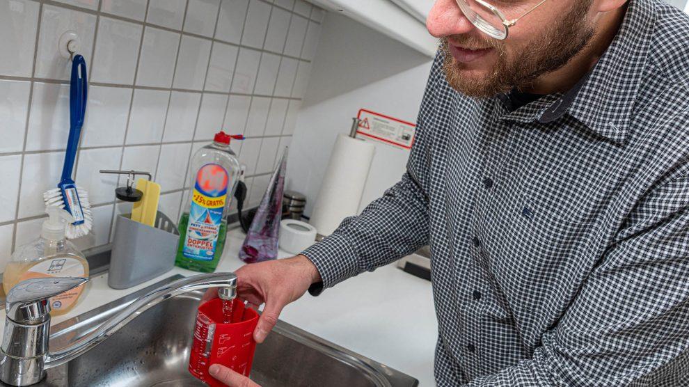 Stefan Sprenger demonstriert die Funktionsweise eines Durchflussmengen-Messbechers. Foto: Gemeinde Wallenhorst / Thomas Remme
