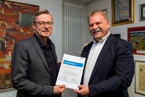 Dr. Reinhold Kassing (rechts) überreicht Bürgermeister Otto Steinkamp die VKU-Mitgliedsurkunde. Foto: Gemeinde Wallenhorst / André Thöle
