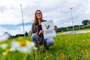Auf Flächen wie dieser blüht es für Bienen, Hummeln und Schmetterlinge, wie Isabella Draber anhand des Hinweisschildes erklärt. Foto: André Thöle / Gemeinde Wallenhorst