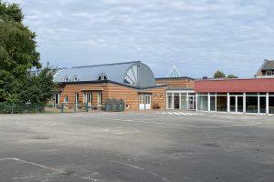 Im gesamten Landkreis Osnabrück ist in der Zeit von 7 bis 17 Uhr auf allen Parkplatzflächen, Verkehrsflächen und Plätzen, die an Schulen und Kindergärten angrenzen, das Tragen einer Mund-Nasen-Bedeckung verpflichtend. Dies gilt auch in Hollage-Ost, wie hier im Bild am Andreaskindergarten und der Johannisschule. Foto: Rothermundt / Wallenhorster.de