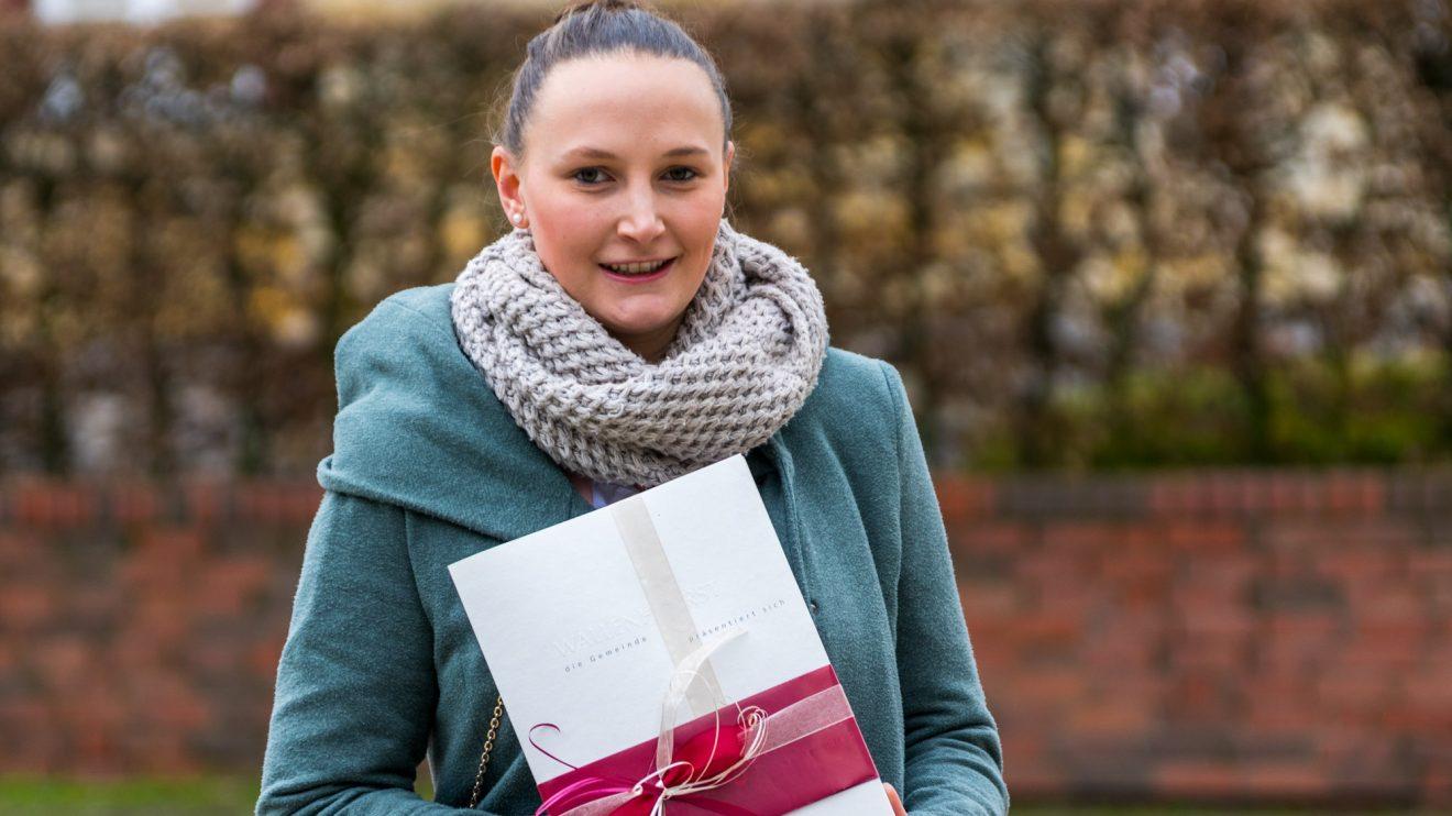 Madeleine Johannes nimmt die Auszeichnung stellvertretend für die 1. Damenmannschaft von Blau-Weiß Hollage entgegen. Foto: André Thöle / Gemeinde Wallenhorst