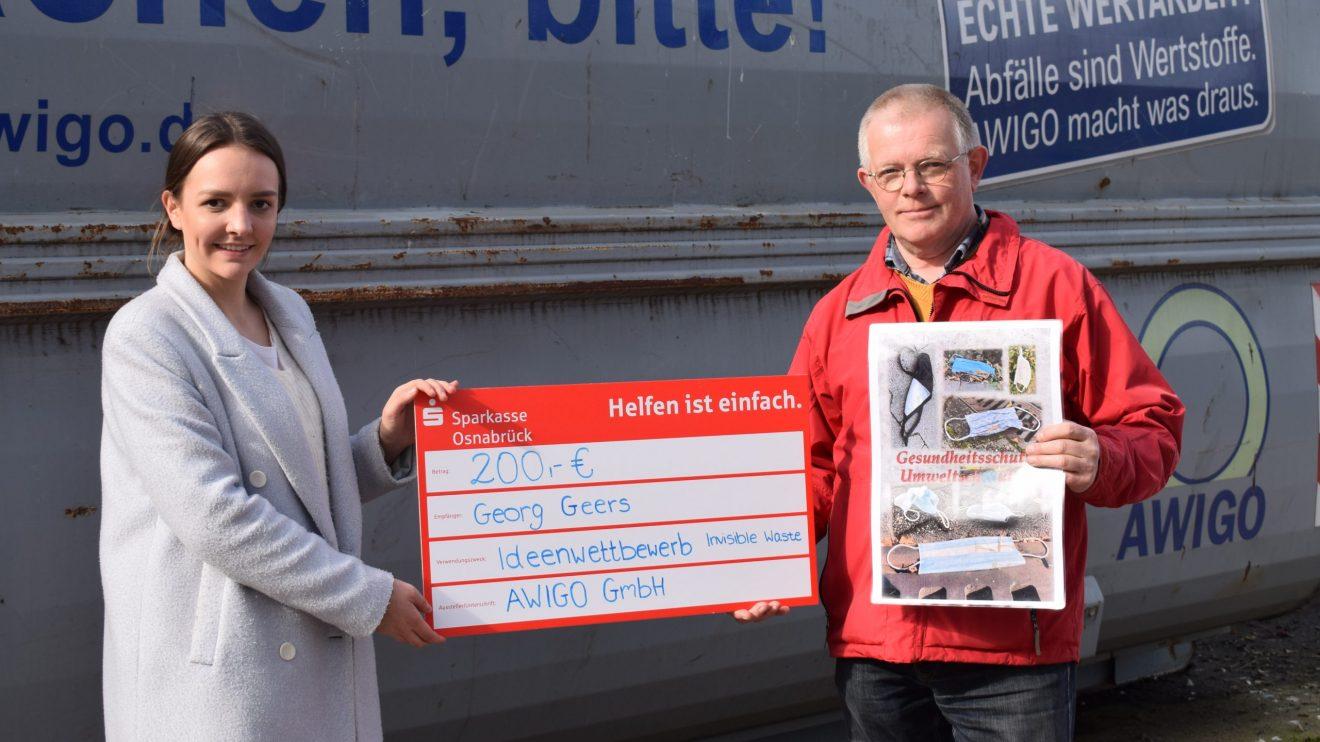 """Emily Meyer (links) aus der Unternehmenskommunikation der AWIGO überreichte Georg Geers (rechts) für seine Fotocollage """"Lost Mask"""" das Preisgeld am Recyclinghof Ankum. Foto: H. Dobelmann / AWIGO"""