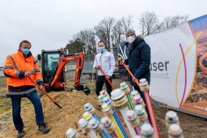René Winter (Geschäftsführer des Bauunternehmens K&R Eilers), Oliver Prostak und Rüdiger Mittmann (von links) greifen zum Beginn des Netzausbaus symbolisch zum Spaten. Foto: André Thöle / Gemeinde Wallenhorst