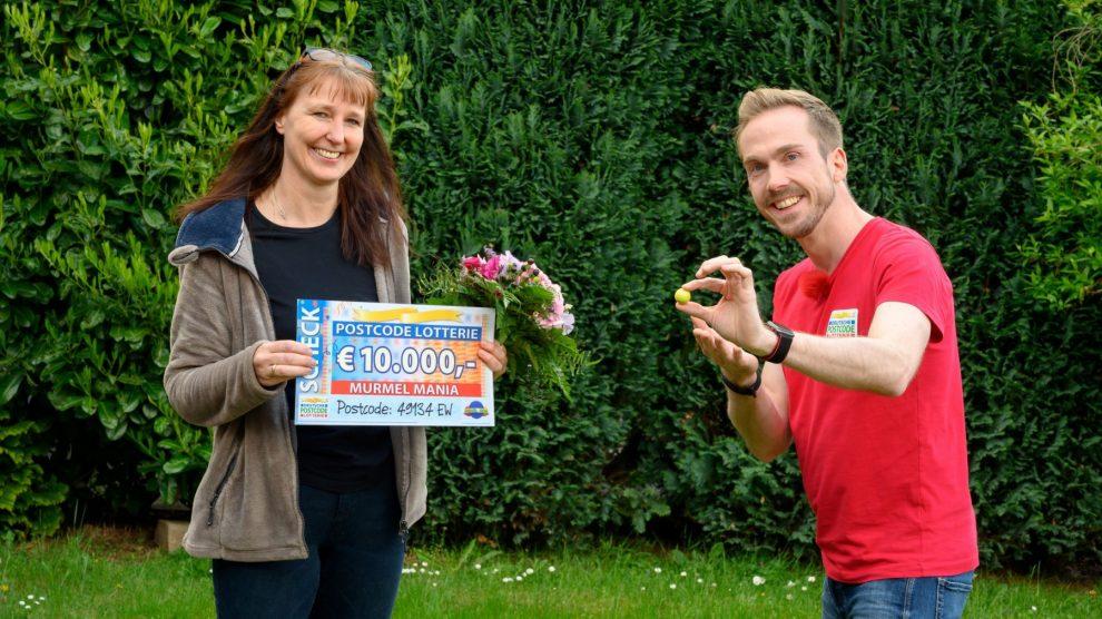 """Straßenpreis-Moderator Felix Uhlig überrascht die 49-jährige Bettina aus Wallenhorst nach der RTL-Sendung """"Murmel Mania"""" mit dem Gewinner-Scheck. Foto: Postcode Lotterie / Wolfgang Wedel"""
