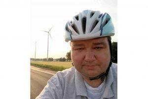 """Holger Pellmann vor den Windkraftanlagen im Gewerbegebiet """"Schwarzer See"""" in Wallenhorst. Foto: CDU Wallenhorst"""