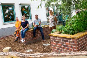 Josef Nölker (Baubetriebshof), Anne Frey, André Schwegmann (Förderverein) und Isabella Draber (von links) im fertiggestellten Schulgarten. Foto: André Thöle / Gemeinde Wallenhorst