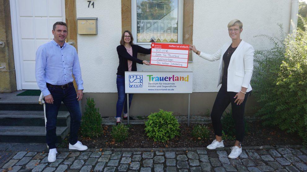 Abteilungsvorsitzender Rainer Brune (l.) und Ehrenamtsmanagerin Jennifer Juber (r.) übergeben den Spendenscheck an Trauerland-Leiterin Marion Gövert. Foto: Marcella Marques