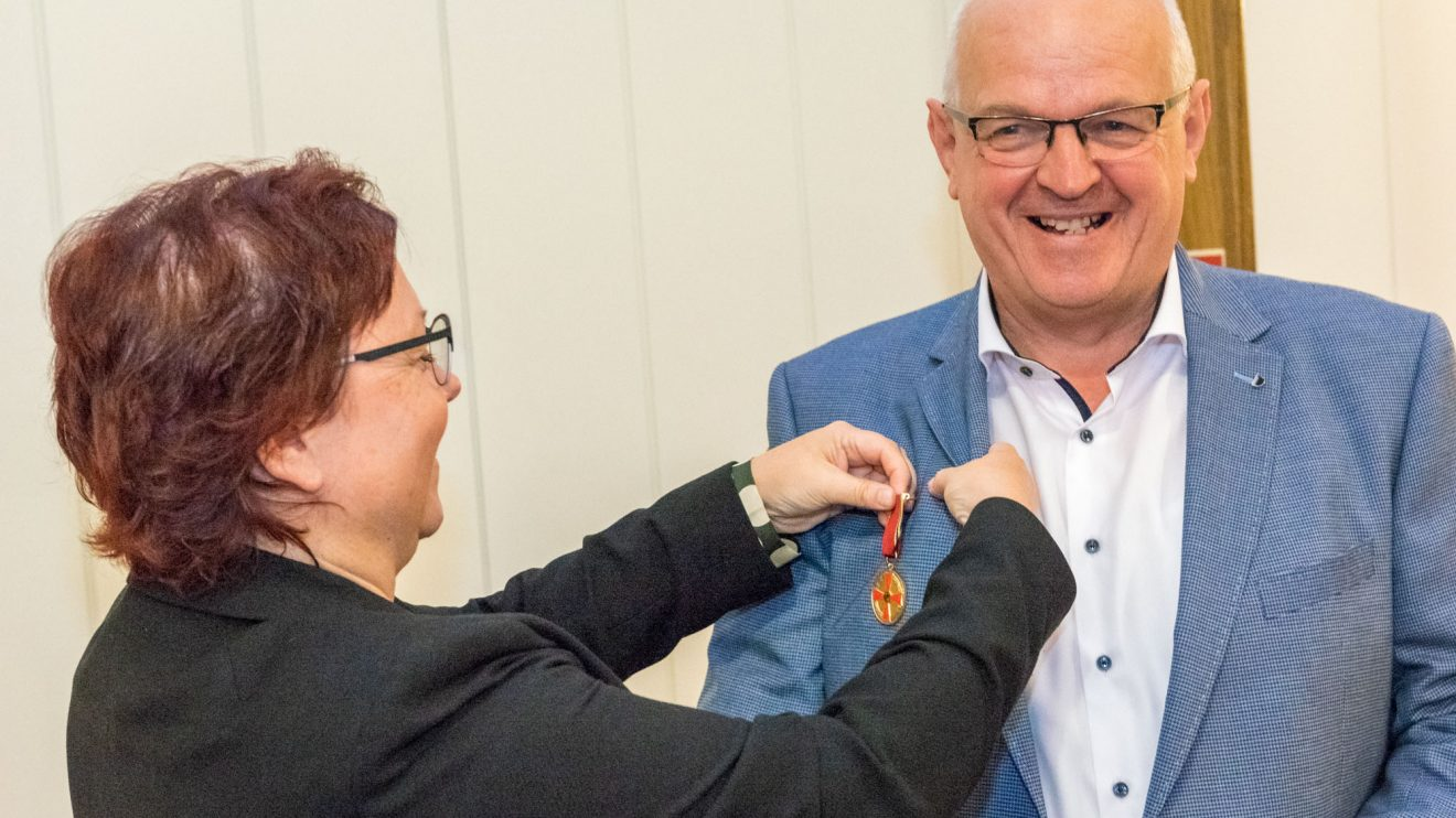 Bärbel Rosensträter überreicht Hubert Wächter die Verdienstmedaille. Foto: André Thöle / Gemeinde Wallenhorst