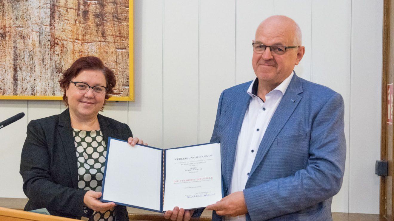 Bärbel Rosensträter und Hubert Wächter mit der Urkunde des Bundespräsidenten. Foto: André Thöle / Gemeinde Wallenhorst